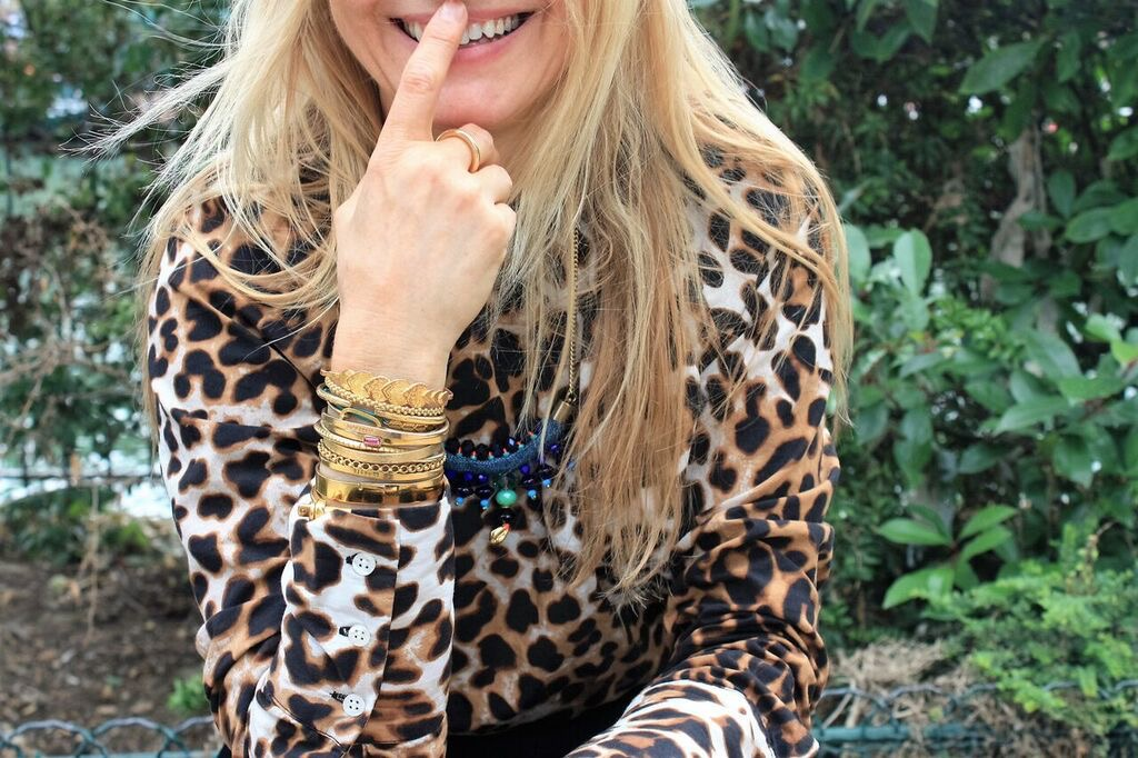woman with jewellry on wrist and leopard print shirt