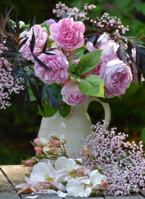 roses and garden flowers in white jugs